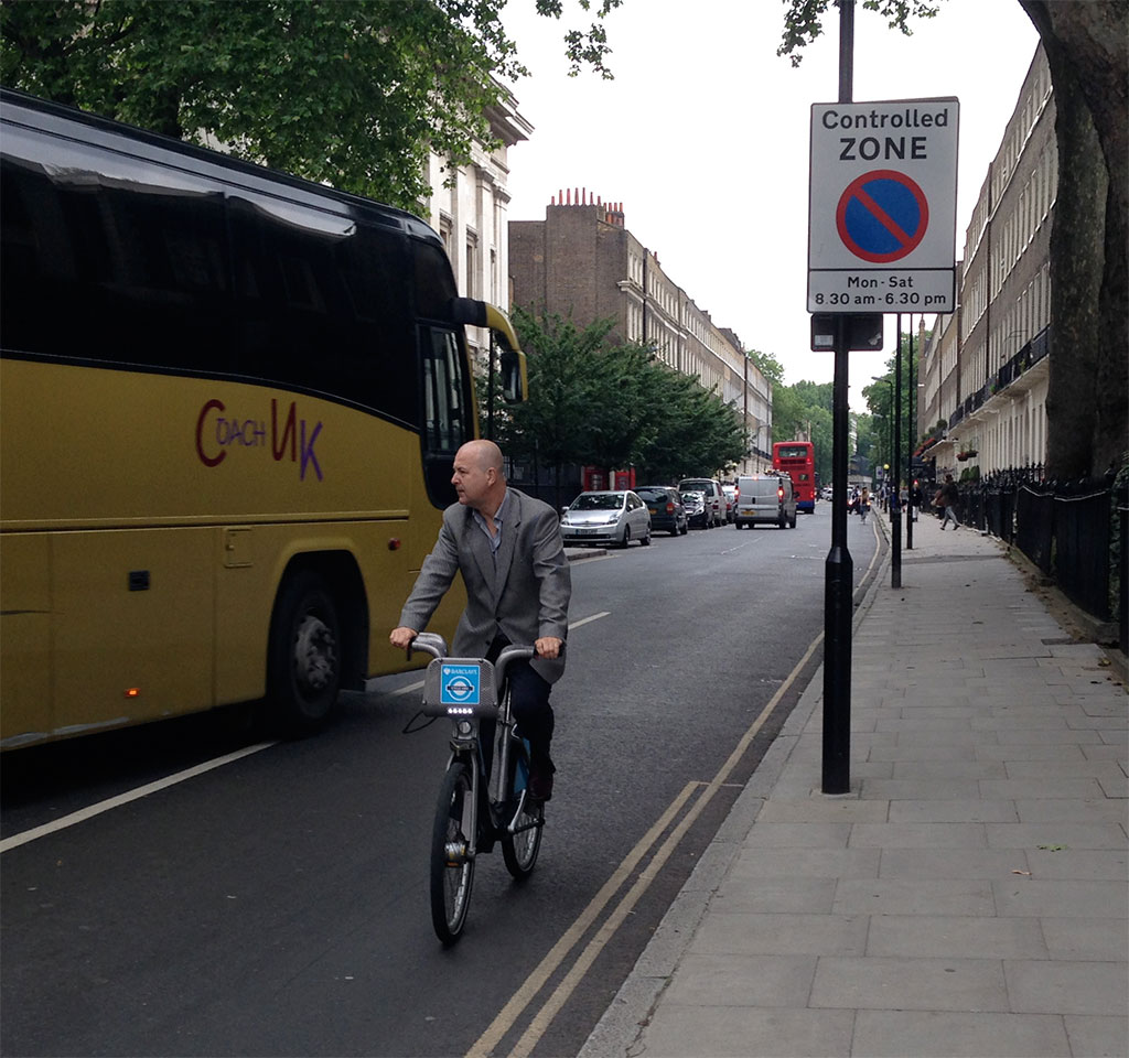 A rider on a Cycle Hire bike dodges a tour bus near the British Museum.