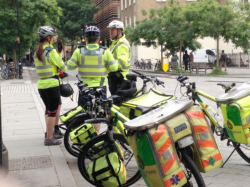 A team of cycling paramedics from the London Ambulance Service confer at street side.