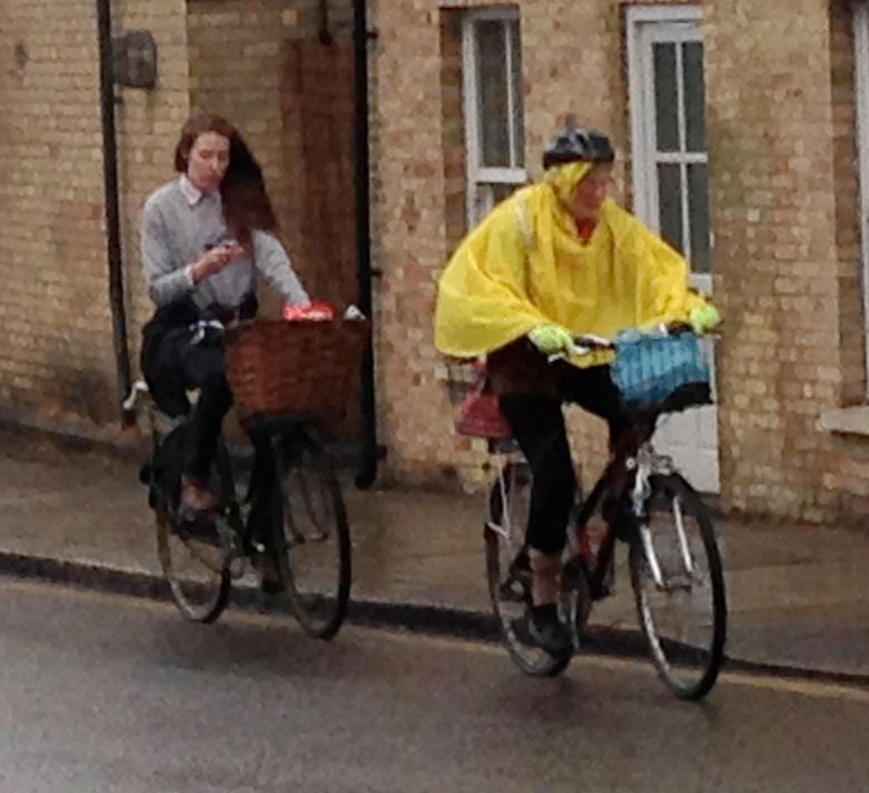 On a rainy afternoon, two cyclists plod up a small hill -- one bundled against the wet and cold, the other blasé about the whole thing.