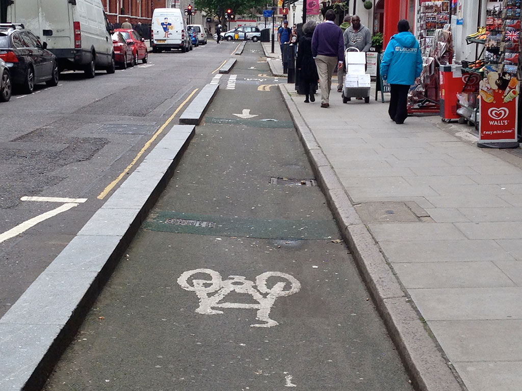 A segregated cycling lane on a narrow London street.